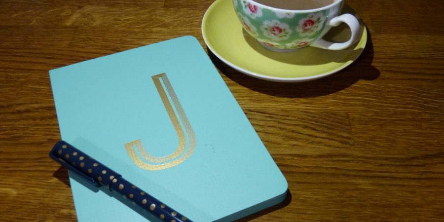 Pen, notebook and cup of tea